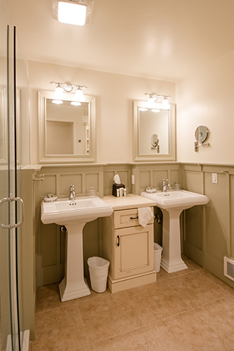 Cottage bathroom with two pedestal sinks