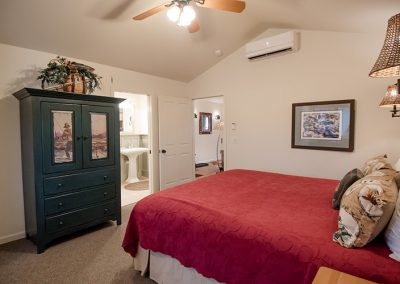Cottage bedroom king bed wth red bedspread and dark armoire