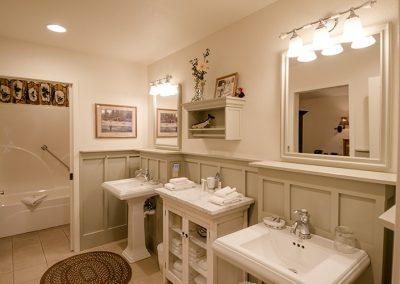 Cottage bathroom with two pedestal sinks and lighting
