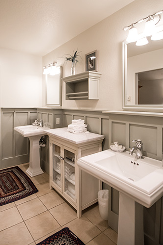 Cottage bathroom two pedestal sinks and lighting