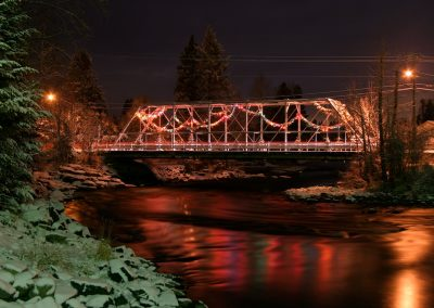 Nighttime view of steel bridge with holiday lights