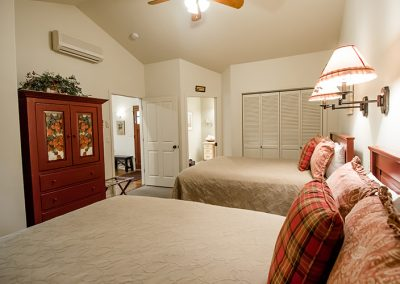 Cottage bedroom with armoire and two full beds